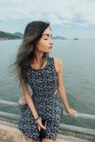 Młoda piękna kobieta w smokingowym obsiadaniu na molu i relaksować z tłem niebieskiego nieba i morza Zdjęcia Royalty Free