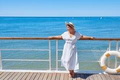 Młoda piękna kobieta w sukni i kapeluszu stojakach na drewnianym molu na tle morze krajobraz Zdjęcie Stock