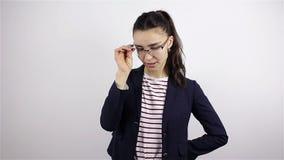 Młoda piękna kobieta w szkieł spojrzeniach przy kamerą i mrugnięciami zbiory wideo