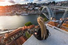 Młoda piękna kobieta z blond dreadlocks spotyka zmierzch na viewing platformie naprzeciw Dom Luis Ja most przez rzekę Obraz Stock