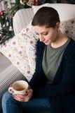 Młoda piękna kobieta z krótkim włosy cieszy się filiżankę herbata, siedzi przed choinką Autentyczny rodziny xmas Zdjęcia Royalty Free