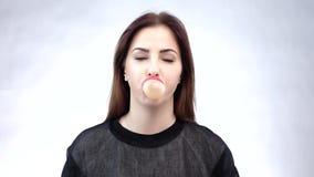 Młoda piękna kobieta z pięknego uśmiechu podmuchowym bubblegum Biały tło swobodny ruch zdjęcie wideo