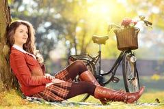 Młoda piękna kobieta z rowerowy relaksować w parku Fotografia Stock