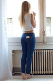 Młoda piękna kobieta z telefonem komórkowym w plecy kieszeni w domu Obraz Stock