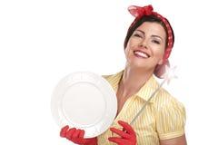Młoda piękna kobiety gospodyni domowa pokazuje magiczną różdżkę na naczyniach fotografia stock
