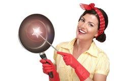 Młoda piękna kobiety gospodyni domowa pokazuje magiczną różdżkę na naczyniach zdjęcie stock