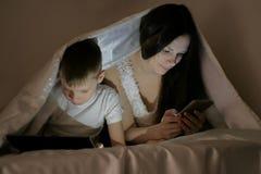 Młoda piękna kobiety mama wyszukuje internet w jej telefonie podczas gdy jej syna dopatrywania kreskówka na pastylce zdjęcie royalty free