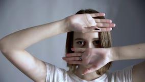 Młoda piękna kobiety pokrywa jego twarz rękami i jego oczu spojrzeniami przy tobą zdjęcie wideo