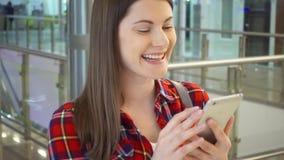 Młoda piękna kobiety pozycja w zakupy centrum handlowego ono uśmiecha się Używać jej smartphone, opowiada z przyjaciółmi zbiory wideo