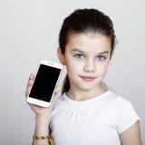 Młoda piękna mała dziewczynka pokazuje nowego mądrze telefon fotografia stock