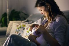 Młoda piękna matka, breastfeeding jej nowonarodzonej chłopiec przy ni Obrazy Stock