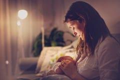 Młoda piękna matka, breastfeeding jej nowonarodzonej chłopiec przy ni Zdjęcie Stock