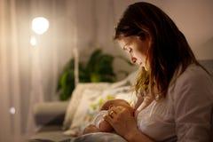 Młoda piękna matka, breastfeeding jej nowonarodzonej chłopiec przy ni Fotografia Stock
