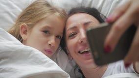 Młoda piękna matka, jej śliczna córka i podczas gdy kłamający na łóżku w domu zbiory wideo