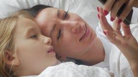 Młoda piękna matka, jej śliczna córka i podczas gdy kłamający na łóżku w domu zdjęcie wideo