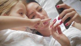 Młoda piękna matka, jej śliczna córka i podczas gdy kłamający na łóżku w domu zbiory