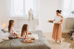 Młoda piękna matka przynosi kakao z Marshmallows i ciastkami jej córki siedzi na łóżku w pełnym zdjęcia stock