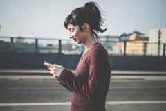 Młoda piękna modniś kobieta używa mądrze telefon Fotografia Royalty Free