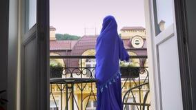 Młoda piękna muzułmańska kobieta w hijab iść balkon i pozycja tam, patrzejący z ukosa zbiory