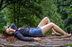 Młoda piękna nastolatek dziewczyna z długie włosy w drelichu i koszula zwiera odpoczywać na drzewie podczas spaceru w parkowym St Fotografia Royalty Free