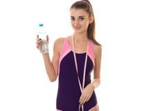 Młoda piękna nikła dziewczyna trzyma butelkę woda i pomiarowa taśma na szyi w ciało kostiumu kąpielowym Obrazy Stock