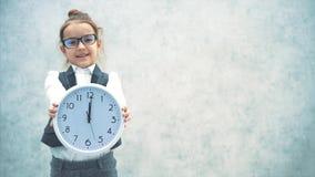 Młoda piękna pani szefowa jest na szarym tle Trzyma biały zegar pokazujący dwanaście godzin Zamykanie, Wolne wideo zbiory