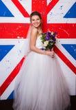 Młoda piękna panna młoda pozuje na anglik flaga Obraz Stock