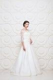 Młoda piękna panna młoda ubierająca ślubna suknia wewnątrz Obraz Royalty Free