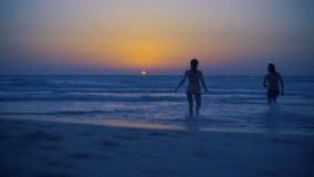 Młoda piękna para biega mistyczny zadziwiający zmierzch na piaskowatej plaży przy półmrokiem Dwa modniś iść w morzu zbiory