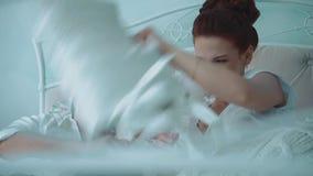 Młoda piękna para ma zabawę w łóżku, przechodzi kamerę wzdłuż łóżka walczą poduszkami, śmiający się, zbiory