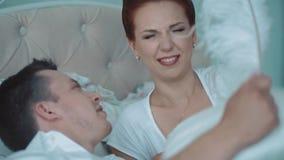 Młoda piękna para ma zabawę w łóżku, walczą z poduszkami, on łaskoczą ona z dużym piórkiem, w górę zbiory