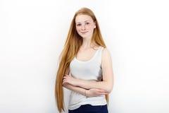 Młoda piękna rudzielec beginner modela kobieta stoi przeciw bielowi w białych koszulka niebieskich dżinsach ćwiczy pozować pokazy Obraz Royalty Free