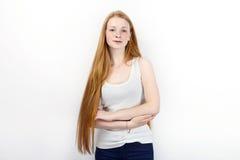 Młoda piękna rudzielec beginner modela kobieta stoi przeciw bielowi w białych koszulka niebieskich dżinsach ćwiczy pozować pokazy Fotografia Royalty Free