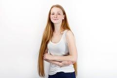 Młoda piękna rudzielec beginner modela kobieta stoi przeciw bielowi w białych koszulka niebieskich dżinsach ćwiczy pozować pokazy Fotografia Stock