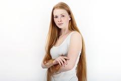 Młoda piękna rudzielec beginner modela kobieta stoi przeciw bielowi w białych koszulka niebieskich dżinsach ćwiczy pozować pokazy Obrazy Royalty Free