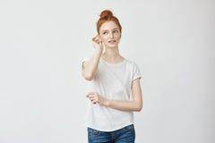 Młoda piękna rudzielec dziewczyna ono uśmiecha się korygujący włosy fotografia stock