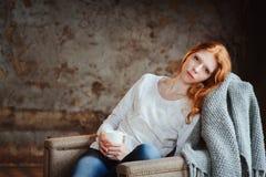 Młoda piękna rudzielec kobieta relaksuje w domu w jesień wygodnym wieczór czytelniczej książce i Zdjęcie Stock