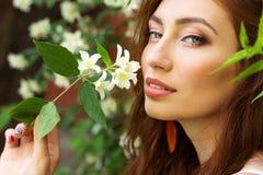 Młoda piękna seksowna dziewczyna z uwodzicielskie duże wargi z długim czerwonym włosianym obsiadaniem w parku blisko drzewnego ja obraz royalty free