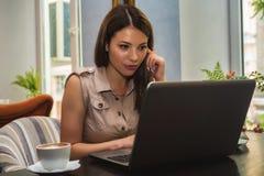 Młoda piękna seruious kobieta pracuje na laptopie w kawiarni fotografia stock