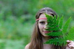 Młoda piękna Slawistyczna dziewczyna z długie włosy i Slawistyczną etniczną suknią zakrywał jej twarz z paprociowym liściem obrazy royalty free