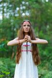 Młoda piękna Slawistyczna dziewczyna z długie włosy i Slawistycznymi etnicznymi suknia stojakami w lato lesie z obrządkowym kindż zdjęcie royalty free