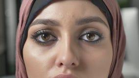 Młoda piękna smutna dziewczyna w różowym hijab i patrzeć kamerę Portret, żeńscy oczy zamyka w górę 60 fps zbiory wideo