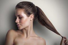 Młoda piękna splendor dziewczyna ciągnie jej długie włosy rękę zdjęcia royalty free