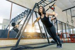 Młoda piękna sporty kobieta ćwiczy na sprawności fizycznej troczy system w gym Sprawność fizyczna, sport, szkolenie i zdrowy styl zdjęcia stock