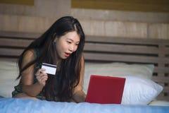 Młoda piękna szczęśliwa Azjatycka Japońska dziewczyna używa karta kredytowa interneta bankowość na laptopie w domu w łóżkowym zak obraz royalty free