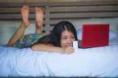 Młoda piękna szczęśliwa Azjatycka Japońska dziewczyna używa karta kredytowa interneta bankowość na laptopie w domu w łóżkowym zak fotografia royalty free