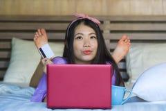Młoda piękna szczęśliwa Azjatycka Japońska kobieta używa karta kredytowa interneta bankowość na laptopie w domu w łóżkowym uśmiec zdjęcia stock
