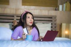 Młoda piękna szczęśliwa Azjatycka Japońska kobieta używa karta kredytowa interneta bankowość na laptopie w domu w łóżkowego zakup zdjęcie royalty free