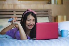 Młoda piękna szczęśliwa Azjatycka Japońska kobieta używa karta kredytowa interneta bankowość na laptopie w domu w łóżkowym uśmiec obrazy stock