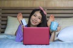 Młoda piękna szczęśliwa Azjatycka Japońska kobieta używa karta kredytowa interneta bankowość na laptopie w domu w łóżkowym uśmiec zdjęcia royalty free